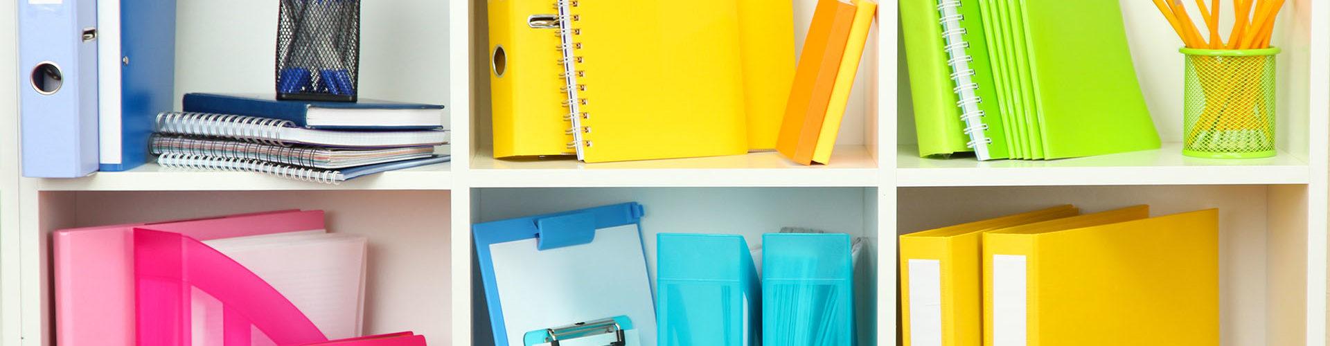 white bookshelf yellow blue pink binders school supplies