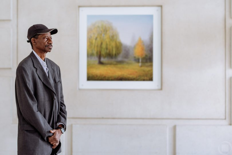 white wall painting african american man baseball hat suit coat