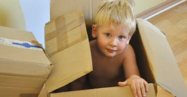 Moving with children tips - blond boy moving box