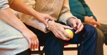 Image of senior's hand using a stress ball while receiving emotional support from a relative